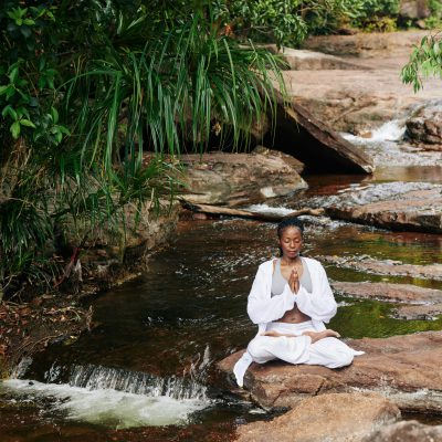 Concentrated woman in white loose cotton clothes meditating in lotus position in secluded place by small forest river